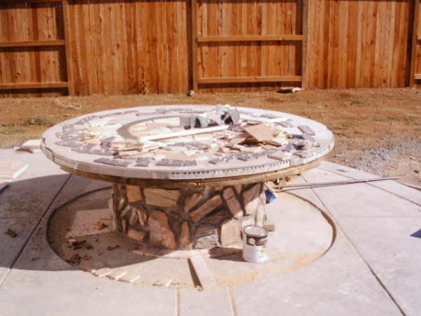 King Arthur's Spool Table, This project started out with a giant wooden spool. We poured the patio with a hole in it (for the table--the hole included a drain for rain and power for lights and a blender) then we dropped in the spool and covered it with travertine tiles that we broke and ground down to smooth the edges. The accents are granite.How much did it cost? About $300. Most of the travertine was scrap (amazing what you can find when you go dumpster diving)., I used a combination of my grinder and wet saw to smooth the edges of each tile. We chose a granite tile that matched our kitchen granite as an accent on the table. We made up the design as we went (but we decided on the two circles of granite fairly early in the design process., Patios & Decks Design