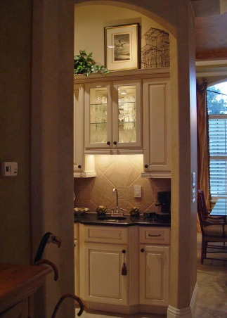 Small but Efficient Kitchen, Thanks to HGTV Angelo & homeowner Andy for choosing my kitchen as an Inspiration Space on RMS the TV show! The galley-style kitchen is part of a big open concept living space. 12 ft. ceiling & tall range hood were a decorating challenge. Video tour and hutch refinishing how-to on my DIY blog at http://www.ratemyfavoritespaces.com. Thanks for stopping by! , Butler's pantry/wet bar area of the kitchen; dining room is to the right. I added the glass shelves & mirror plus the halogen lighting inside and above the cabinet. , Kitchens Design