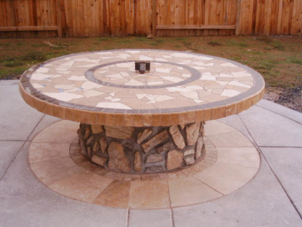 King Arthur's Spool Table, This project started out with a giant wooden spool. We poured the patio with a hole in it (for the table--the hole included a drain for rain and power for lights and a blender) then we dropped in the spool and covered it with travertine tiles that we broke and ground down to smooth the edges. The accents are granite.How much did it cost? About $300. Most of the travertine was scrap (amazing what you can find when you go dumpster diving)., Instructions. 1) Get a spool2) Cut it down to the right height3) Bathe it in wood protector to deter rotting4) Run power from your house to the center of the table 5) The patio hole will fill up with water so add a drain 6) Cover the table in tar paper chicken wire and 'float' it level7) Tile the table8) Cover the vertical areas with mesh wire and cultured stone9) Ensure wife likes it (mine brings out the best of me)10) Invite 12 people over. Add libations. Enjoy., Patios & Decks Design