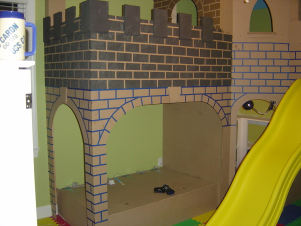 "Castle Playroom, Bedroom to playroom conversion.  Two story castle has toy storage in the ""dungeon"" and underneath the oversized cushioned lounging area. Floor to ceiling tower is actually a climbing wall.  Castle surface is textured to give it a stone block appearance.  Upstairs is a magnetized chalk board.  Removable slide. The castle has rope lighting throughout.  Foam tiles are used for flooring.  The Cabana-style window/closet treatments have rolled-up center panels that can be closed. , Boys' Rooms Design"