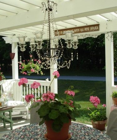 Cottage style pergola, We had our pergola built last summer but designed it ourselves.  We stained the wood white had the top covered with corrigated frosted plastic to keep out the rain and give us some shade.  Almost all the furniture was bought from garage sales and repainted.  The patio table and chairs were brought back to life by covering them with rainproof fabric.  Fairy lights and candles give us just enough light for an evening meal.  I love geraniums and filled the space with them. , Patios & Decks Design