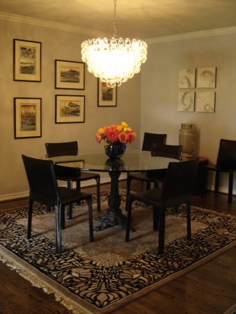 Serene Glam Dining, Romantic and elegant dining room that proves that a glamourous space doesn't have to be fussy. A soft lavender gray is on the walls to provide a serene light while the hand-blown glass chandelier adds a spark of glamour. The glass top table helps give a feeling of space while the black leather chairs and Art Deco area rug ground the space., Dining Rooms Design
