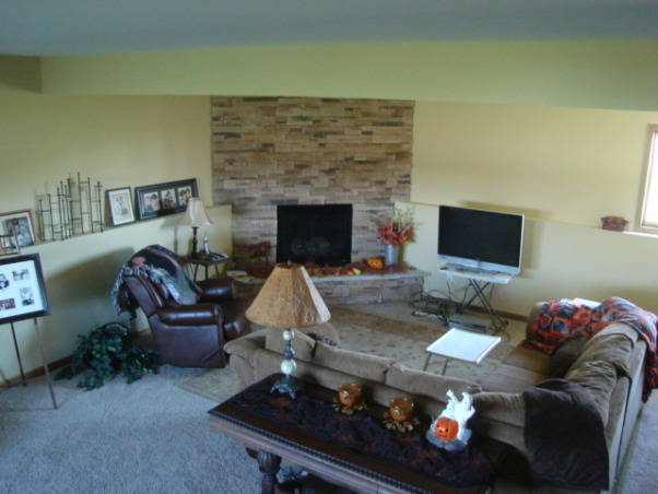 Lower Level Family Room, I recently moved from California to Indiana.  We purchased a Bi-Level home but I have no clue how to decorate around the ledge that surrounds the rooms in the lower level.  Currently I am just using it to prop up family photos.  I am fortunate to have nine foot ceiling and a beautiful stacked stome corner fireplace.  The room is large it measures 20' x 29' bu I feel cramed into one end of it., , Living Rooms Design