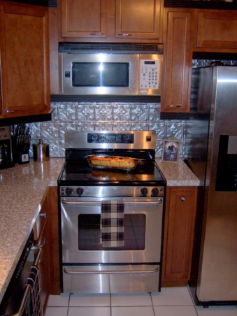 safari kitchen , very small working kitchen  9 x 10   tin backsplash maple cabinets and simulated granite countertops the black trim accents the appliances, , Kitchens Design