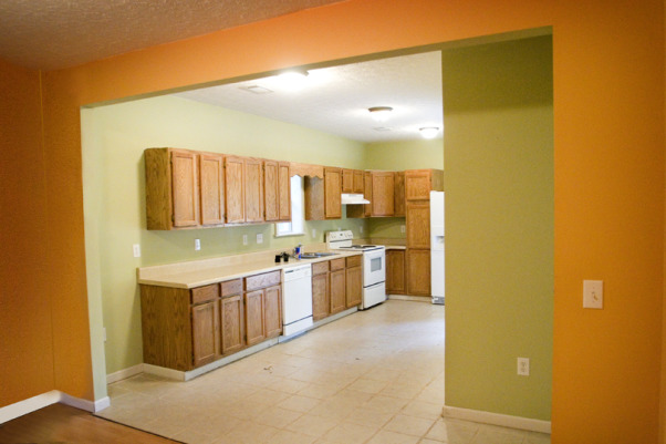 Classic Traditional Modern Kitchen with Black Cabinets, Our kitchen started out with pale green walls and the cheapest stock oak cabinetry you can buy.  We added moulding to the tops of the cabinets and painted them black. We also added a beadboard backsplash and dark chocolate laminate wood floors.  There is still plenty of work to do & stainless steel appliances to buy but here's where we are as of today!  For more photos and videos of our little fixer upper visit our website: www.TheLetteredCottage.net, KITCHEN - BEFORE       , Kitchens Design