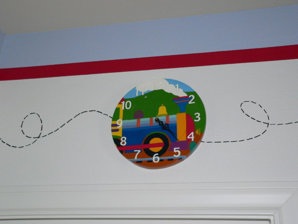 Train-Themed Toddler Boy Bedroom, My 2.5 yr old son's room was a boring tan so I decided to liven it up a bit.  The ceilings are high - 10' - so I painted a 3' high border to bring the room down to scale.  There are 23 different train cars hand-painted with acrylic paint and I added some accents in patterned scrapbook paper to enhance the design.  All of the furniture is from Pottery Barn except for the reading chair which is from Ikea.  The rug and bedspread (where I got the train inspiration) are from The Land of Nod., , Boys' Rooms Design