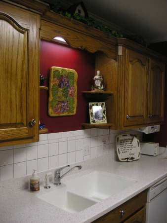 Vineyard Theme Kitchen, I love the deep reds and golds.  Since my living room is also decorated in those colors and open to the eating area of my kitchen it was important that the colors flow., Changed out the traditional counter and went with the solid surface with integrated sink and love it!  Also enjoy having the mini shelves above sink to display special photos and trinkets.  My husband and I came upon the handpainted artwork which show grapes with a wine bottle.  We were able to have the artist add our last name to the wine label which gives a more personalized look in our kitchen., Kitchens Design