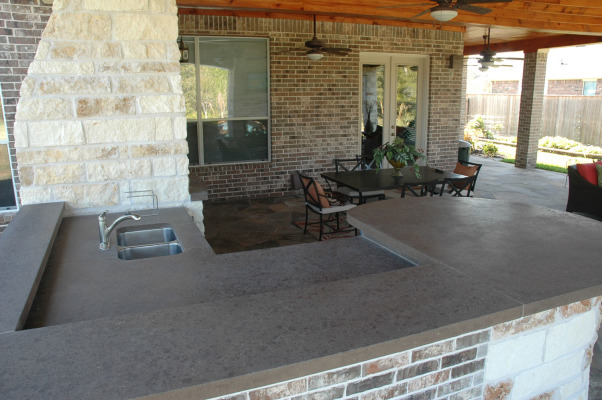 Texas Style Outdoor Room / Kitchen, We like to spend time outdoors but in Houston Texas you need a covered space and pool to keep cool most of the year. We designed our outdoor living space to be an extension of the indoors. It includes a sitting area dining area and outdoor kitchen.  We would love to hear what you think!(The palm design over the fireplace is not artwork.  It is a flat screen tv cover.), Polished Concrete Countertops, Patios & Decks Design