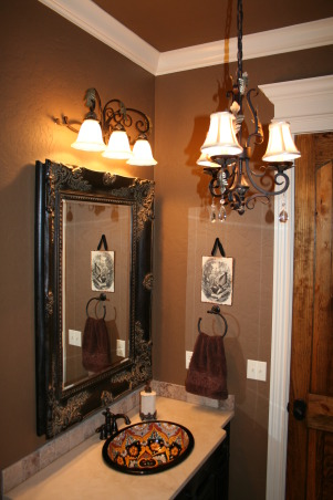 "Elegant Powder Room, We currently have this home on the market. It is located in Missouri in the Branson School District. For more information and to look at a virtual tour, the MLS number is 341835. Would make a great permanent residence or vacation home. I chose to have the powder room painted ""Sweet Georgia Brown"".  It is a small space but I wanted to use a rich color on both the walls and ceiling.  The vanity is stained black and distressed.  The sink is a talavera from Mexico.  I chose travertine for the countertops and backsplash.  The artwork came from a flea market and the colors work well with the sink.  The mirror was from a local antique store.  , Bathrooms Design"