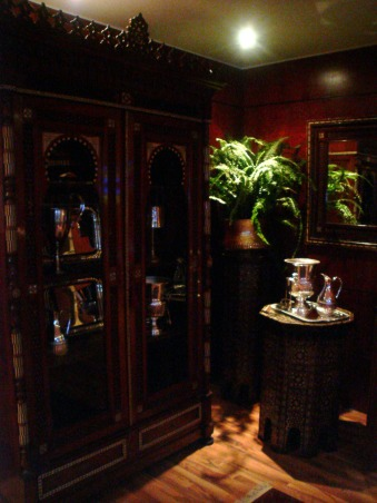 Hotel Cigar Lounge, We took a modern cramped billard room with laminate floors and wood panelling we could not change and garage door style windows and created a Cigar Lounge for a hotel on the Red Sea in Egypt.  We covered the windows with sheet rock and 2 specially made windows based on a 19th century original brought in original Egyptian antiques handmade carpets and had comfortable couches created.  We designed the tables based on elements of original ones and added antique pictures. , , Living Rooms Design