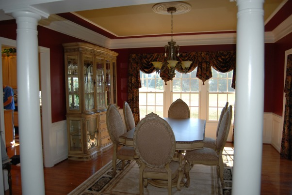 Burgundy Dining Room, This is a beautiful dining room done in red (burgundy) walls with white columns. The color scheme is brought together with a black and nuetral rug nuetral furniture and black burgundy and nuetral color window treatments. The room is accentuated with shadow boxes below the chair rail and decorative molding on the ceiling. The ceiling is also painted a complimentary nuetral color., Dining Rooms Design
