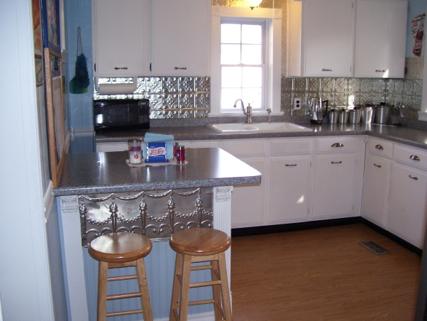 My Folk Victorian Kitchen Redo, Cost only about 2000 dollars for kitchen interior redo! Saved by using existing cabinets and appliances(appliances are newer) then added new hardware counters flooring lights window trim sink faucet plumbing wainscoting new breakfast bar built using existing leftover cabinet all new door and cabinet trim etc..  I tried to use trim to remind of an old victorian kitchen. I got very good deals off Ebay and did all the work myself.  , The satin nickel backsplash came from American Tin Ceilings an online company.  It was only about  $15 for a 2X2 sheet was easy to install and only cost about 120 bucks or so.  The torch tin on the bar is new old stock I got off Ebay for 20 bucks.  The bar surface is great not only for a quick bite but for a preparation surface., Kitchens Design