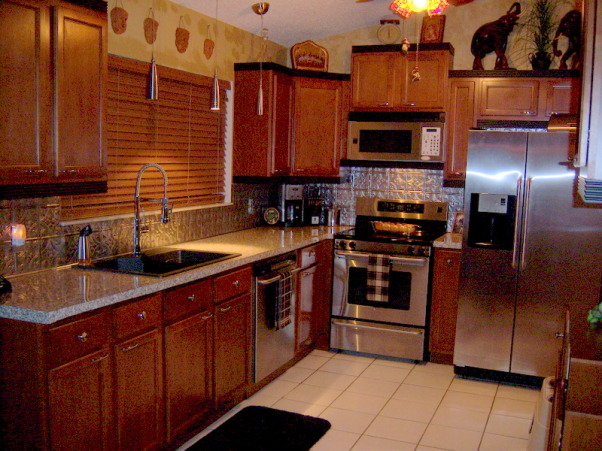safari kitchen , very small working kitchen  9 x 10   tin backsplash maple cabinets and simulated granite countertops the black trim accents the appliances, newly remodeled kitchen  feb 20 2008  cost of all 4238.58  except appliances bargin shoppin in so. fla , Kitchens Design