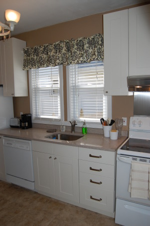 small budget kitchen remodel, 75 year old bungalow home with a small galley kitchen.  Ikea cabinets with silestone countertops and new tile floors update this functional space.  would have loved new stainless steel appliances...maybe later., , Kitchens Design