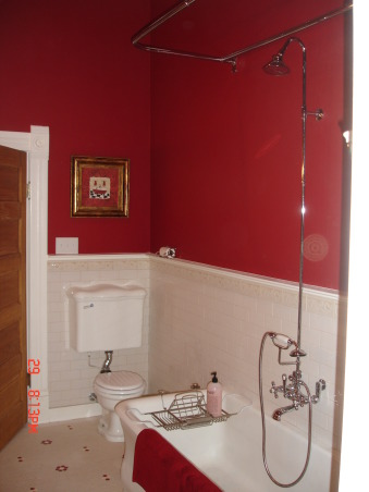 Vintage Red Bathroom, Master Bathroom of our lakehouse.  , Since this photo I have made a custom shower curtain from yellow and red toile along with a valance to match.  The tub and toilet are original to the house and both date from 1913., Bathrooms Design