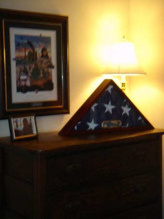 """USMC tribute to our son, Our son Albert was killed in Iraq in January 2006.  Since that time we are attempting to find a new """"normal"""" to our lives.  We are in the process of re-evaluating each room in order to simplify our home.  We recently finished our son's bedroom in time for Veteran's Day 2008.  We strived to keep the room as a tribute rather than a shrine to our fallen Marine., On this dresser is the flag that was presented to us to the left is a picture of Albert when he was training for Iraq in the Mojave Desert and on the wall is a collage with Albert's picture and various events from Operation Iraqi Freedom., Bedrooms Design"""