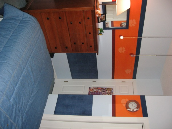 Sports / School team theme room , My 4 year old son loves sports and ClemsonUniversity.  This room is an attempt to combine both in a way that will hopefully grow with him and last until he goes to college.  Clemson's main color is bright orange However it is a small room too so I didn't want to paint the whole thing orange.  The lower navy blue band of color around the room is a denim paint technique and then I painted accent stripes of a deep red and navy.  , , Boys' Rooms Design