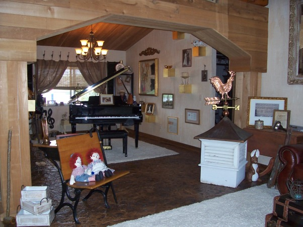 Our Orlando Home Turned Rustic Cabin, Our passion for elegance combined with the feeling of a rustic mountain lodge has turned our Orlando home into a very green and unique space.  We brought the outside in in more ways than one!, Our long living room extends to an area where a beautiful black baby grand piano is showcased!  There are gold wooden blocks on the walls by the piano with family pictures in gold frames throughout the room.  A matching cream poofy rug ties the two areas of the living room together!, Living Rooms Design