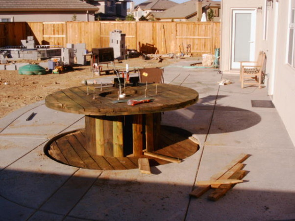 King Arthur's Spool Table, This project started out with a giant wooden spool. We poured the patio with a hole in it (for the table--the hole included a drain for rain and power for lights and a blender) then we dropped in the spool and covered it with travertine tiles that we broke and ground down to smooth the edges. The accents are granite.How much did it cost? About $300. Most of the travertine was scrap (amazing what you can find when you go dumpster diving)., We put in a drain under the table and a lot of gravel so that if water got inside it would have a place to go. We also and ran power out to the table (you need a place to plug in those lights and that blender)., Patios & Decks Design