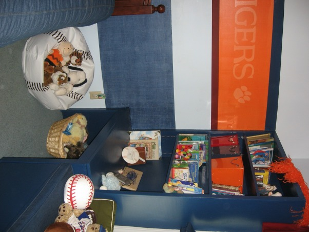 "Sports / School team theme room , My 4 year old son loves sports and ClemsonUniversity.  This room is an attempt to combine both in a way that will hopefully grow with him and last until he goes to college.  Clemson's main color is bright orange However it is a small room too so I didn't want to paint the whole thing orange.  The lower navy blue band of color around the room is a denim paint technique and then I painted accent stripes of a deep red and navy.  , As you can see my son loves stuffed animals and has alot of books as well so itdoes clutter up the built in shelves a bit.  Eventually we are going to add shelves along the upper navy blue stripe (above the orange stripe) for him to place knick knacks etc... (They will be like the shelves in my daughter's room- see ""Pink and Green Paradise for pictures), Boys' Rooms Design"