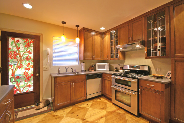 Wow Factor Floor,  kitchen was 1950's .  We added cabinets to ceiling height w/glass insert accent doors  s.s  appliances & exposed a pine sub-floor. which we scored  and stained . Added recessed lighting Corian counter  wine rack  , kitchen after showing door film treatment , Kitchens Design