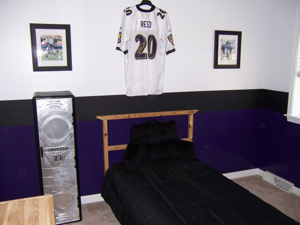 Ravens Football Room!, Being huge Baltimore Ravens fans when it came time to re-do our sons room there was no other option  for us! The Raven purple is on the bottom black in the center and white on top.The black paint in the middle is actually chalkboard so our son can keep scores and stats on the wall. We were going for the running scoreboard look.All the prints and the jersey are signed by men who play for the best team!My husband made the 6 square wall unit. , Boys' Rooms Design