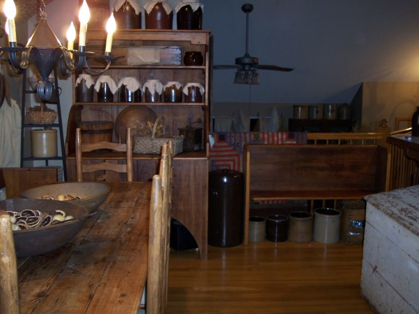 "Country Primitive Dining Room, Here are some pictures of our dining room. I know there is allot to look at...lol But this is the way we like it. I love all the old things....they give me such a ""homey"" feel. We just finished our ""remodel"" on the Dining Room about 6 months ago. Nothing needed to be done but to make this house our home this is what we have done....We add new fixtures boarding up the ceiling & painting the walls & trim. , This is looking from the back 12 pane glass door into our Living Room. You can see the ceiling fan & behind the bench is a banister., Dining Rooms Design"