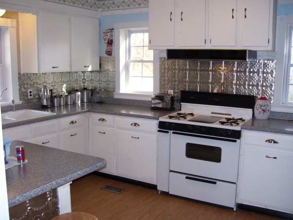 My Folk Victorian Kitchen Redo, Cost only about 2000 dollars for kitchen interior redo! Saved by using existing cabinets and appliances(appliances are newer) then added new hardware counters flooring lights window trim sink faucet plumbing wainscoting new breakfast bar built using existing leftover cabinet all new door and cabinet trim etc..  I tried to use trim to remind of an old victorian kitchen. I got very good deals off Ebay and did all the work myself.  , Tons of light from 3 new double hung vinyl windows.  The nickel hardware is from an Ebay company and were only $1.09 to $1.49 each!  I had the Whirlpool stove ordered from Sears a few years ago for about  $650.  It has a griddle in the middle which can be changed to a 5th burner and storage on the left..  The hood was $30 from a local building supply store that sells buyouts.  The canisters ($20) are old from Ebay and yes I still make my coffee with a perculator I paid $7 for, Kitchens Design