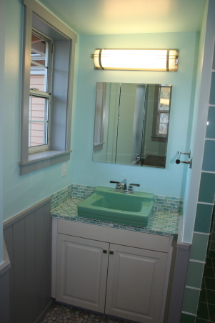 Master Bath Remodel--Sad Victorian to Mid-Century Fabulous, With five shower-only bathrooms in our former B&B farmhouse, putting in a bathtub was key. The existing room was a mix of 80's gold trim and flowery Victorian pink and blue.  Living on an island we wanted a beach vibe, and I wanted a  retro blue or green tub and sink. I found a Ming Green American standard suite that was found in an old barn on a neighboring island and took the design cues from that., The sink, with custom built vanity, 'Galaxy' space age light fixture, salvaged medicine cabinet found in our shed, and counter and backsplash with modwalls Lush glass tile Santa Monica blend., Bathrooms