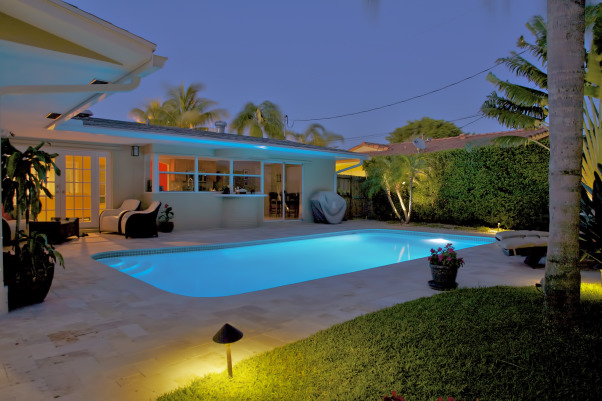 "Gloomy to Sunny, Pool and deck were totally redone along with landscaping.  Pool was retrofitted with LED lighting and deck was covered in an elegant travertine stone.  Landscaping uses exotic plants and trees from South Florida, Asia, Brazil and the Caribbean while breaking the previous straight lines and producing a more ""flowing"" curved space. , At night, the pool's LED and landscape lighting makes the yard a perfect place to entertain or swim. , Outdoor Spaces"