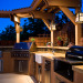 Outdoor Kitchen and Eating Area, Our backyard is small (21x52) and we made the most out of the space we have.   We love to sit outside with a glass of wine and enjoy the evening., Outdoor kitchen island with pergola and low voltage (12-volt) pendant lights.  Counters are made of colored concrete.  Poured offsite by a concrete counter company - 2.5 inches thick.  Backsplash is glass tile (basket weave design).  Pergola is made of redwood and stained/painted.               , Outdoor Spaces